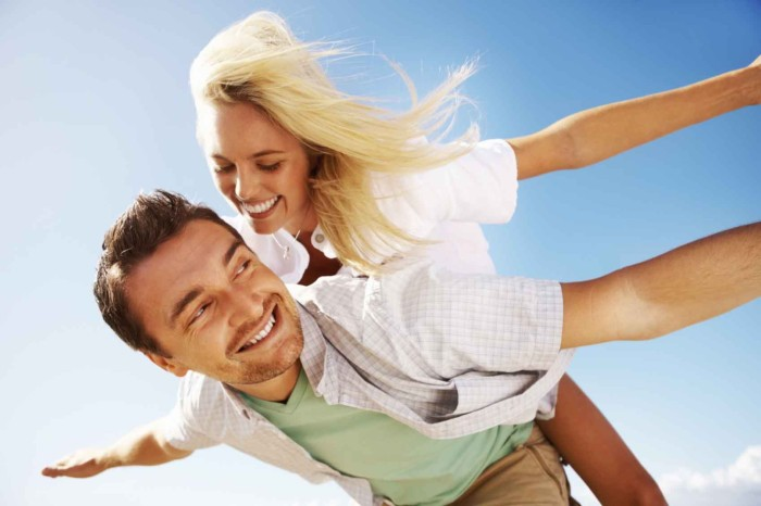 Beautiful couple having fun and stretching arms against sky
